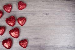 Red and white glitter hearts on wooden background Royalty Free Stock Photography