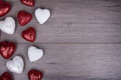 Red and white glitter hearts on wooden background Royalty Free Stock Images