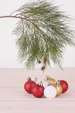 Red, white and gold Christmas baubles and pine tree branch Stock Photo
