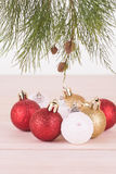 Red, white and gold Christmas baubles and pine tree branch Stock Images