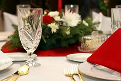 Red, White, Gold Table Setting. Festive table setting with red and white linens and crystal glasses.  Floral arrangement and candle in background.  Gold utensils Stock Image