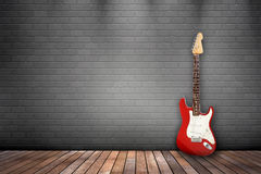 Red and white guitar on gray wall. Red and white guitar against a grey brick wall.  Wooden flooring Royalty Free Stock Image