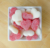 Red and White Gummy Hearts in White Bowl on Butcher Block. Red and white gummy hearts fill a white bowl royalty free stock image