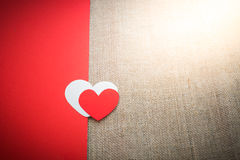 Red and white heart on half of red paper and sackcloth  backgrou Royalty Free Stock Image