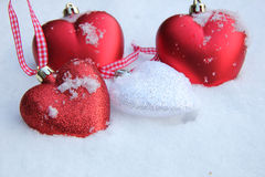 Red and white heart ornaments in snow Royalty Free Stock Image