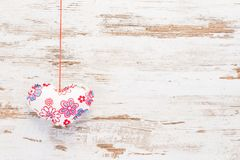Red and white heart on vintage wood. Red and white handmade heart on a string at a vintage wooden background. Can be used for postcard, wishing posts and Stock Photos