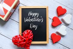 Red and white heart wooden handcraft and box white a blackboard written with Happy Valentine`s day. Top view of red wooden handcraft heart symbol,box of present stock image