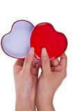Red and white hearts in two hands Stock Photo
