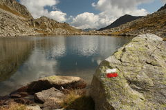 Red and white hiking mark at glacial lake in Aragon Pyrenees Stock Photography