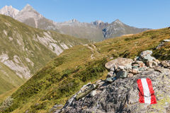 Red and white hiking trail marker in Austrian Alps Royalty Free Stock Photo