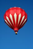 Red and White Hot Air Balloon. A red and white hot air balloon soars in a clear blue sky Royalty Free Stock Images