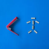 Red and white isolated metal stapler tool on blue background stock image