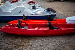 Red and white kayaks on the sand. Boats for leisure sailing laying on the beach. Kayak adventure trip. Extreme sports. Relaxing ti. Red and white kayaks on sand Stock Photos
