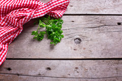 Red and white kitchen towel  and green parsley leaves on rustic Stock Photo