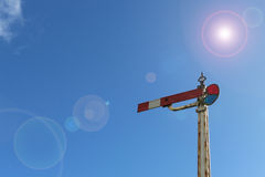Red and white lamplight semaphore signal in blue sky with lens f. Red and white lamplight semaphore signal in blue sky with lntentional lens flare Stock Photos