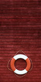 Red and white life buoy on the side of a wooden ship Stock Images