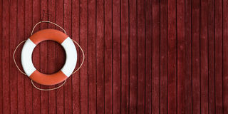 Red and white life buoy on the side of a wooden ship Royalty Free Stock Images