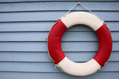 Red and White Lifebuoy on a Blue Background. Red and White Lifebuoy hanging on a blue painted wooden fence panel stock photos