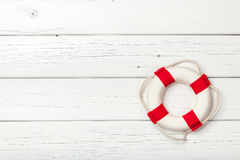 Red-white lifebuoy on white wooden board. Copy space Stock Images
