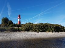 Red and white lighthouse against blue sky royalty free stock photo