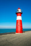 Red and white lighthouse against a bright blue sky Royalty Free Stock Photos