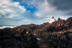 Red and white lighthouse among angular rocks in front of the sea. A red and white lighthouse sits on top of a beautiful rock formation looking at  the sea Royalty Free Stock Images