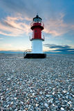 Red and white lighthouse on a beach with pebbles Stock Photography