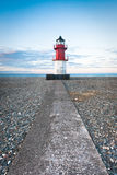 Red and white lighthouse at the end of a path Stock Images