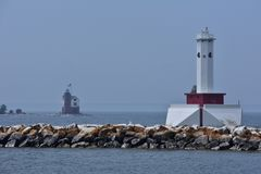 Red and white lighthouse on Great Lakes looking at second lighthouse stock images