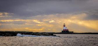 A red and white lighthouse on an island surrounded by storm clouds stock photos
