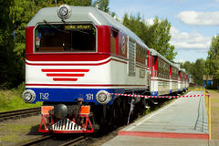Red-white locomotive with trailer cars passenger stands on a platform in the forest. Locomotive, painted in blue-white-red color, stands on the rails among the Stock Images