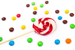 Red-white lollipop with colorful button-shaped chocolates on the white background. Royalty Free Stock Photos