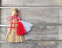 Red and white martenitsa on old wooden background. Red and white martenitsa with broom on old wooden background with lace Stock Photography