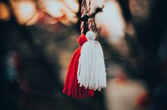 Red and white martisor hanging on the branch closeup stock photo