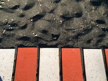 Red and White Metal Planks on Black Sand stock image