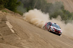 Red and white Mitsubishi Lancer on rally Stock Photography