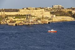 A motorboat passes along St. John`s Demi-Bastion at Fort Ricasoli, Kalkara Malta. A red and white motorboat passes along St. John`s Demi-Bastion, Fort Ricasoli Royalty Free Stock Image