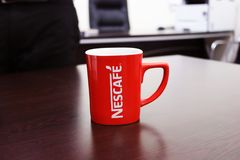 Red and White Nescafe-printed Mug on Brown Wooden Table Stock Image