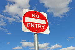 Red and white No Entry sign in a blue sky Stock Photo