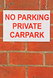Red and white No Parking Private Carpark sign on brick wall Royalty Free Stock Image