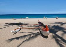 Red and white outrigger on a Hawaiian beach. Red and white outrigger at peopleless Kauna'oa Beach, Hawaii Royalty Free Stock Image