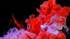 Red and white paint underwater. Colorful white and red paint drops mixing in water stock footage