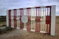 Red and white painted metal gate in Dungeness, Kent Stock Image