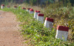 Red and white painted milestones. In range on a country road under the sunlight Royalty Free Stock Images