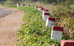 Red and white painted milestones. In range on a country road under the sunlight Stock Photo