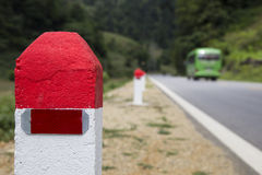Red and white painted milestones in range on a country road Stock Photos