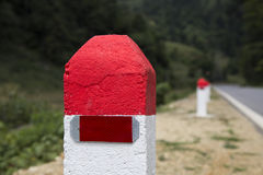 Red and white painted milestones. In range on a country road under the sunlight. Concept of purpose and target, long term and the way to achieve success Stock Image