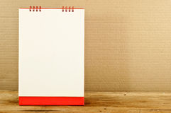 Red and white paper calendar on a wooden table. Royalty Free Stock Photography
