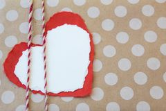 Red and white paper hearts tied to a polka dot kraft paper backing with twine. Copy space, horizontal aspect Stock Image