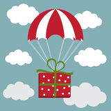 Red and white parachute with the present in the sky. Delivery Co Royalty Free Stock Photos